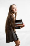 Schoolgirl in uniform carrying heavy stack of books Royalty Free Stock Images