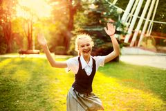 Schoolgirl in uniform with pigtails joyful dancing at sunset i stock image