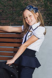 Schoolgirl in uniform waiting for the bus to school Stock Image