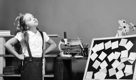 Schoolgirl with unsatisfied face expression in her classroom. Girl stands near blackboard with colored sticky notes. Childhood and study time concept. Kid and royalty free stock images