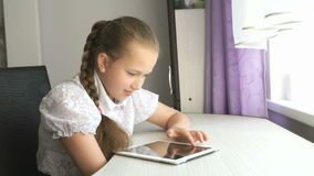 Schoolgirl uses a digital tablet computer at home stock footage