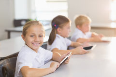 Schoolgirl using digital tablet in classroom. Happy schoolgirl using digital tablet in classroom at school Stock Photography