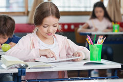 Schoolgirl Using Digital Tablet In Classroom. Little schoolgirl using digital tablet with classmates in background at classroom Royalty Free Stock Photos
