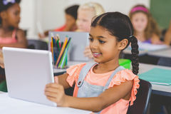Schoolgirl using digital tablet in classroom. At school Royalty Free Stock Image