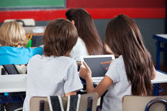 Schoolgirl Using Digital Tablet At Desk Stock Photo