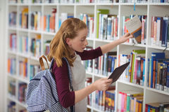 Schoolgirl using digital tablet while selecting book in library Royalty Free Stock Photos