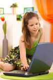 Schoolgirl using laptop at home Stock Photo