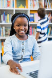 Schoolgirl using laptop in library. At school Royalty Free Stock Image