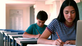 Schoolgirl using laptop while studying in classroom. At school stock video footage