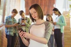 Schoolgirl using mobile phone in corridor Stock Photography