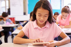 Schoolgirl using tablet computer in elementary school class Royalty Free Stock Images
