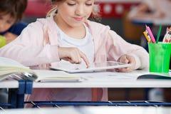 Schoolgirl Using Tablet At Desk. Little schoolgirl using digital tablet at desk in classroom Royalty Free Stock Photo