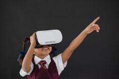 Schoolgirl using virtual reality headset against blackboard Stock Image