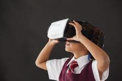 Schoolgirl using virtual reality headset against blackboard Royalty Free Stock Images