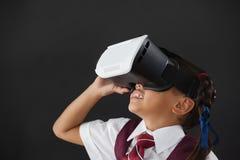 Schoolgirl using virtual reality headset against blackboard Royalty Free Stock Photo