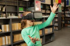 Schoolgirl using virtual reality headset in library. Front view of Caucasian schoolgirl using virtual reality headset in library at elementary school stock image