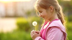 Schoolgirl on vacation. Summer vacation. A sweet girl blowing on a dandelion. Dandelion seeds fly in the wind. Children stock footage