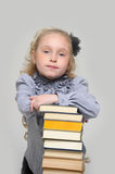 Schoolgirl with a very high stack of books Stock Photography