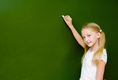 Schoolgirl wants to write something on the blackboard Stock Photography