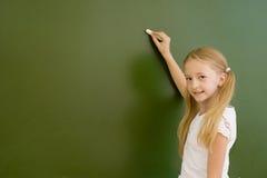 Schoolgirl wants to write something on the blackboard Stock Photos