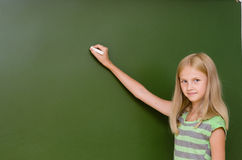 Schoolgirl wants to write something on the blackboard Royalty Free Stock Photography