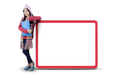 Schoolgirl in warm clothes leans on billboard Royalty Free Stock Photography