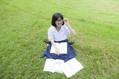 Schoolgirl was reading on the lawn. Stock Photography