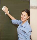 Schoolgirl washes chalkboard Stock Photography