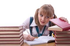 Schoolgirl is watching furtively textbook. Royalty Free Stock Images