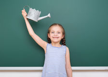Schoolgirl with watering can play near a blackboard, empty space, education concept Royalty Free Stock Photo