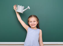 Schoolgirl with watering can play near a blackboard, empty space, education concept Royalty Free Stock Photos