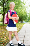 Schoolgirl is on the way to school for the first time. Cute schoolgirl in blue dress is going to school for the first time Stock Photos