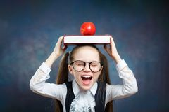 Schoolgirl Wear Glasses Carry Book Apple on Head royalty free stock photography