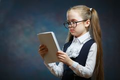 Schoolgirl Wear Glasses Uniform Look at Notebook royalty free stock image