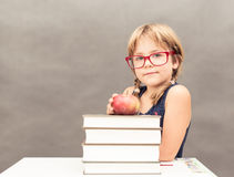 Schoolgirl wearing glasses sitting at a table with a stack of th stock images
