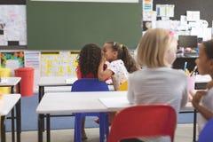 Schoolgirl whispering into her friend ear in classroom at school. Rear view of schoolgirl whispering into her friend ear in classroom at school stock photos