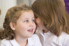 A schoolgirl whispers to her friend in a class Stock Image