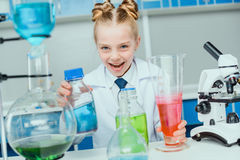 Schoolgirl in white coat making experiment with reagents. In science laboratory stock images