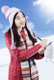 Schoolgirl in winter wear writes on clipboard Royalty Free Stock Image