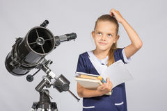 Schoolgirl wondered and looked up to by reading a textbook while standing at the telescope Stock Image