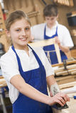 Schoolgirl in woodwork class. Smiling royalty free stock photography
