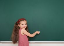 Schoolgirl write on school board Royalty Free Stock Photos
