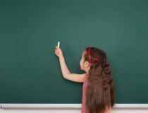 Schoolgirl write on school board Stock Image