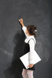 Schoolgirl writes on the blackboard . Stock Photography
