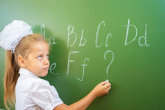 Schoolgirl writes English alphabet with chalk on blackboard Royalty Free Stock Images