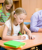 Schoolgirl writes the exam in class Stock Images