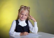 Schoolgirl writes. Schoolgirl in school uniform writing at the table Royalty Free Stock Photo