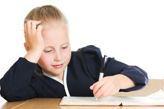Schoolgirl writes at a table Stock Photo