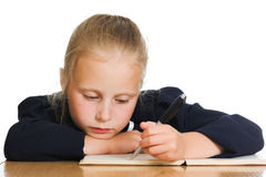 Schoolgirl writes at a table Royalty Free Stock Photo