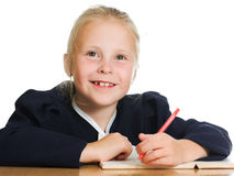 Schoolgirl writes at a table Royalty Free Stock Photography